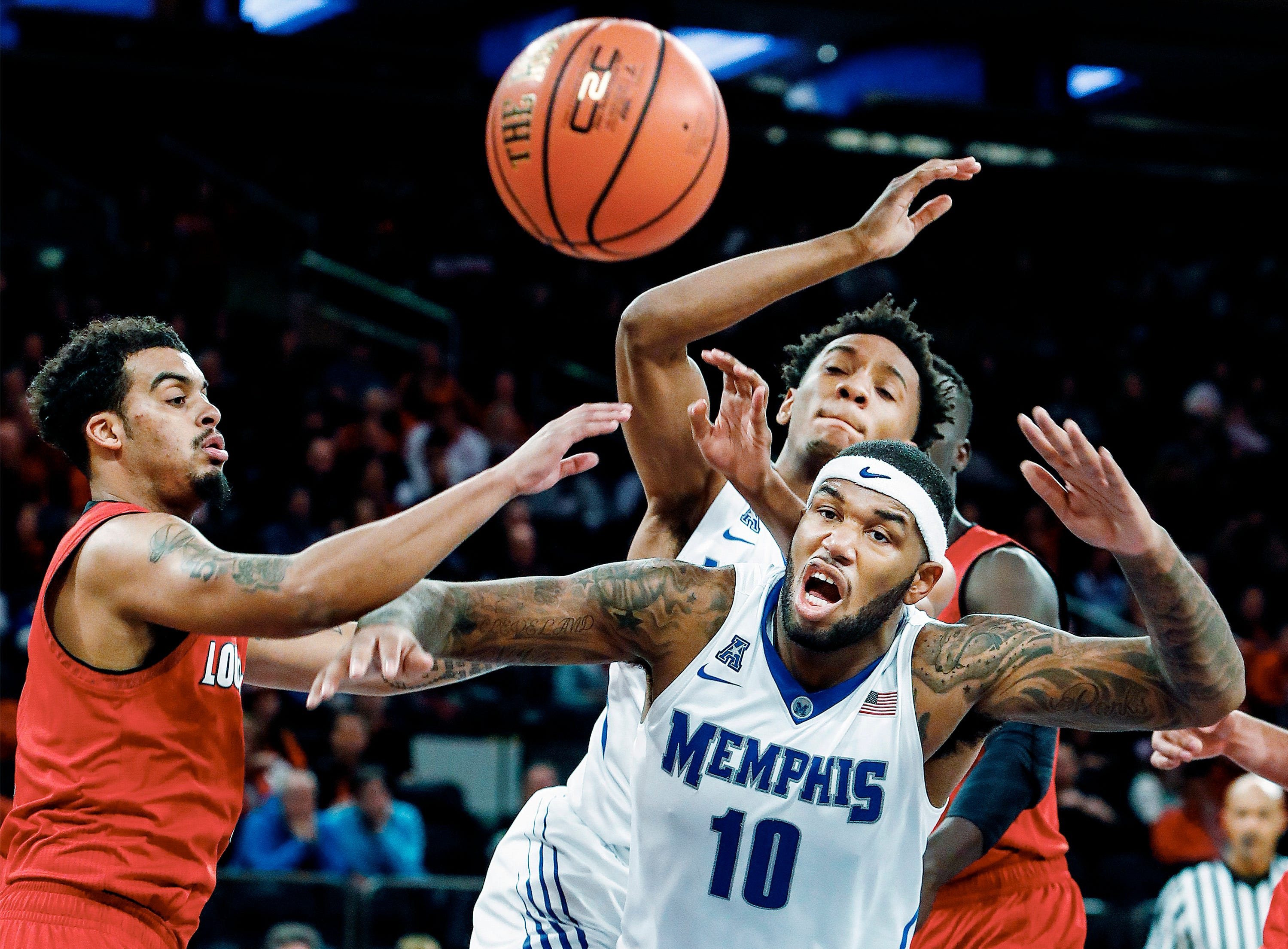 Memphis teammates Mike Parks Jr. (bottom right) and Jamal Johnson (top right) can not hang onto a rebound against Louisville defender Quentin Snider (left) during second half action at Madison Square Garden in New York, Saturday, December 16, 2017.