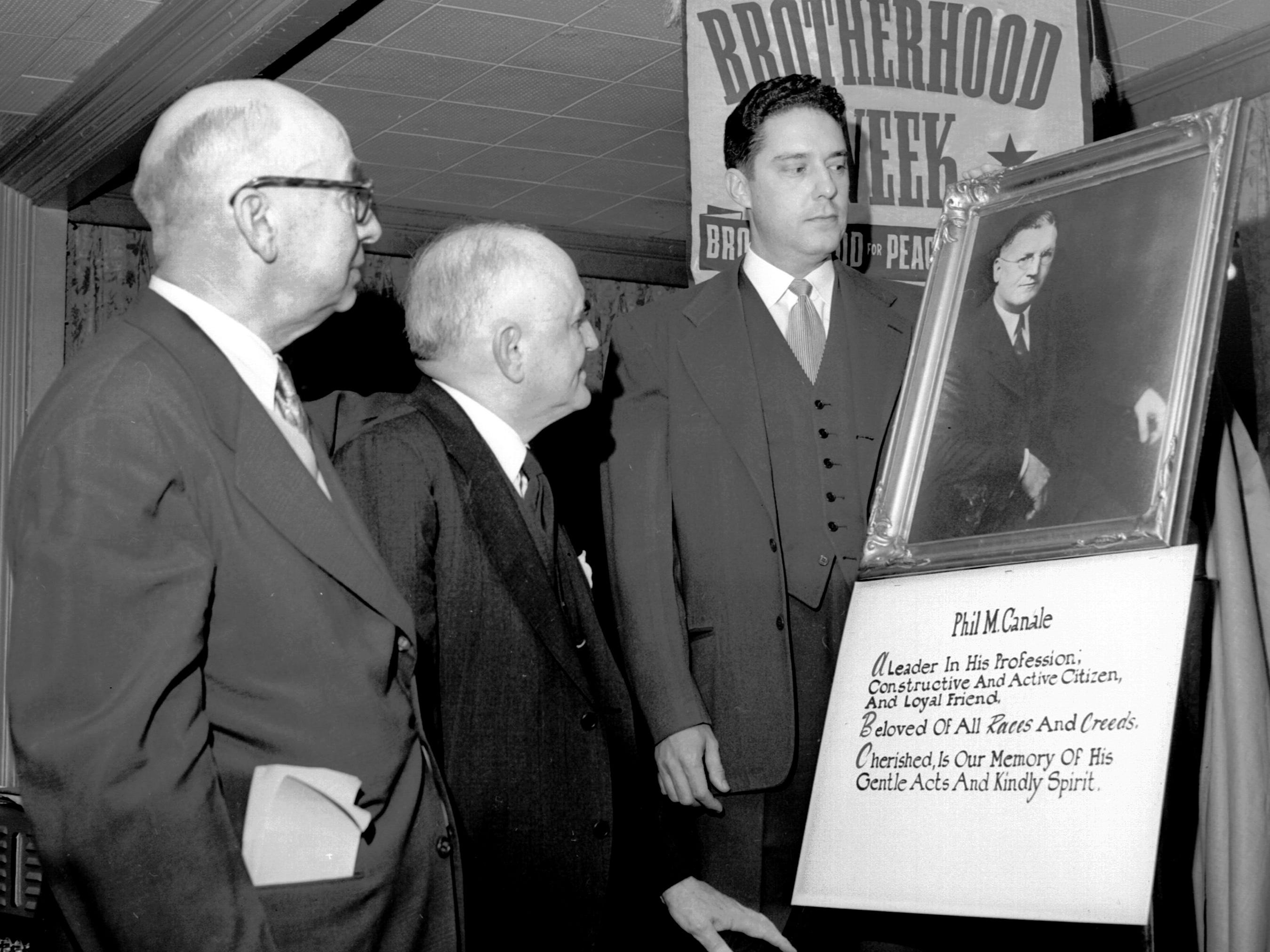 Presentation to his family of a large framed portrait of the late Phil M. Canale Sr. highlighted a memorial ceremony at The Peabody Feb. 16, 1952 by Shrine Luncheon Club honoring the attorney and civic leader. Walter Chandler, center, Shriner and former mayor, presented the portrait, which was accepted for his family by Phil M. Canale Jr., right. W. B. Hill, left, luncheon club president, presided at the ceremony.