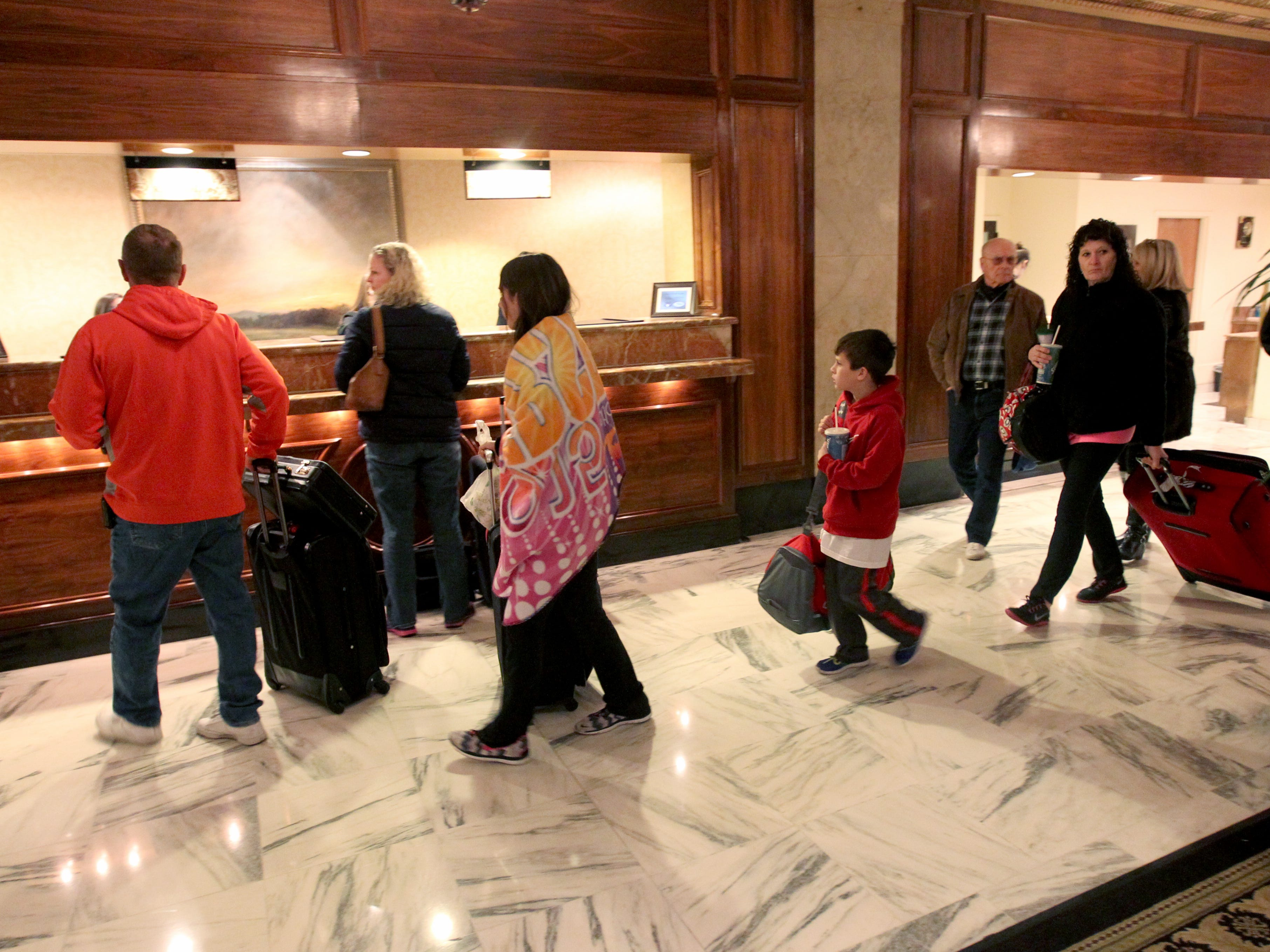 Hotel guests Barry Scroggins, left, his daughter Hannah Scroggins, 14, center, nephew Diego McCormick, 11, center right, and wife Lisa Scroggins, right, check in to the registration counter at the Peabody Hotel on Feb. 16, 2015. Memphis area hotels had the highest occupancy rate in more the 25 years in 2014.