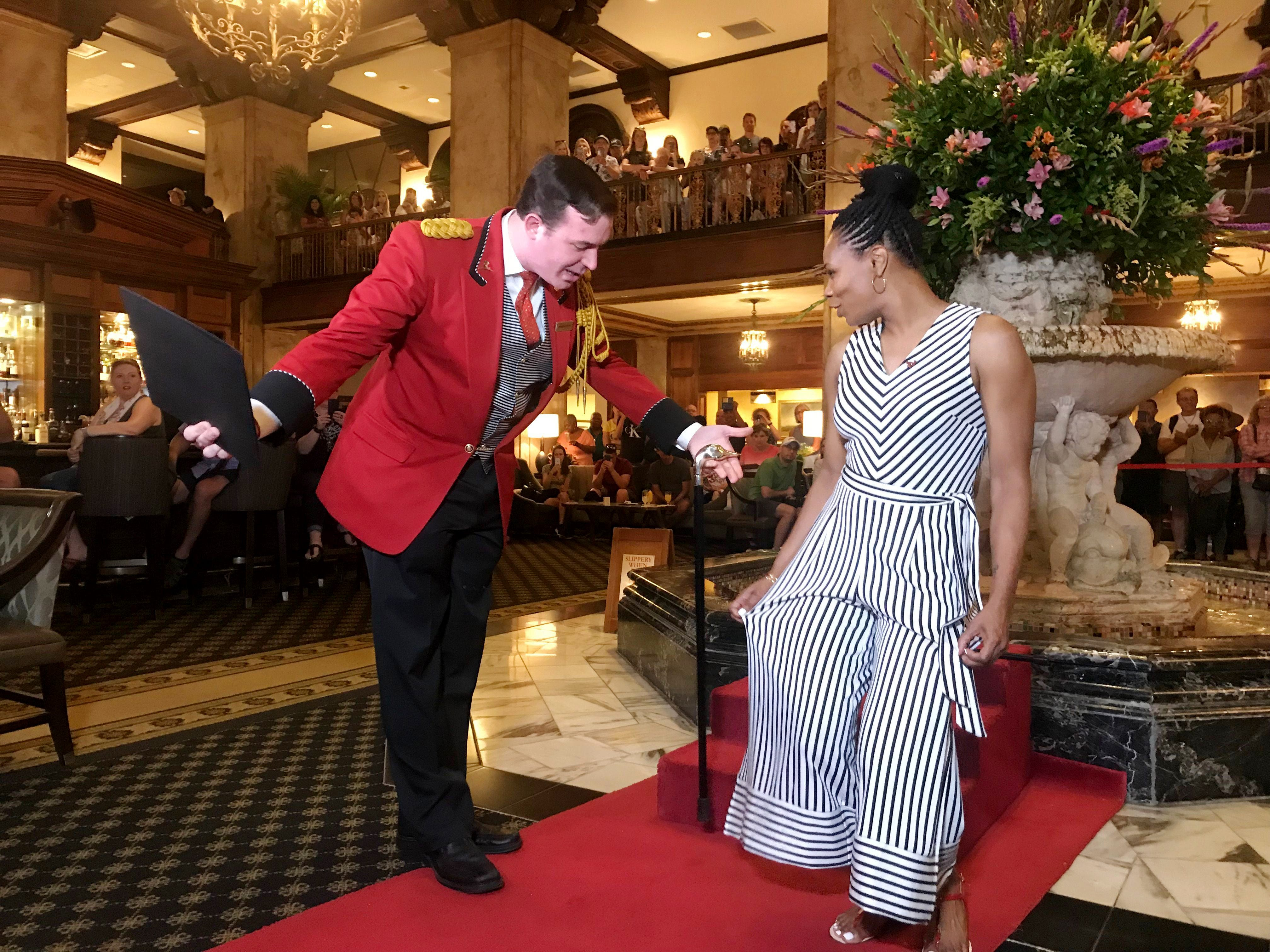 Peabody Hotel Duckmaster Anthony Petrina, left, bestows the duckmaster cane and certificate to Memphis resident Lashara Wheeler on June 6, 2018, in the Grand Lobby of the Peabody Hotel. Wheeler was named honorary duckmaster after hotel staff saw her saving eight ducklings from a storm drain in a viral video.