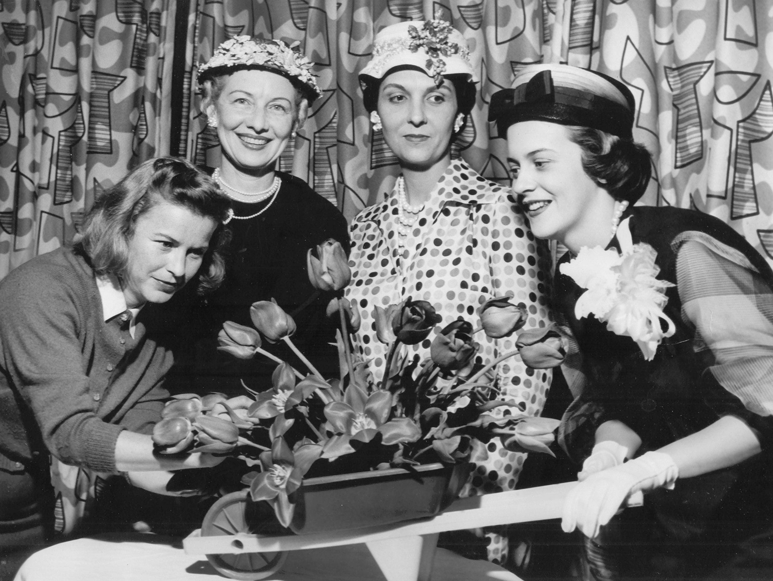 Mrs. Allan Fisher, left, puts last-minute touches on table decorations for a luncheon at the Peabody on April 9, 1959, honoring candidates for the Miss City Beautiful title. Looking on are Mrs. Allan Redd, second from left, Mrs. Leonard Pierotti, party chairmen, and Miss Florence Ann Wilkins, retiring Miss City Beautiful.