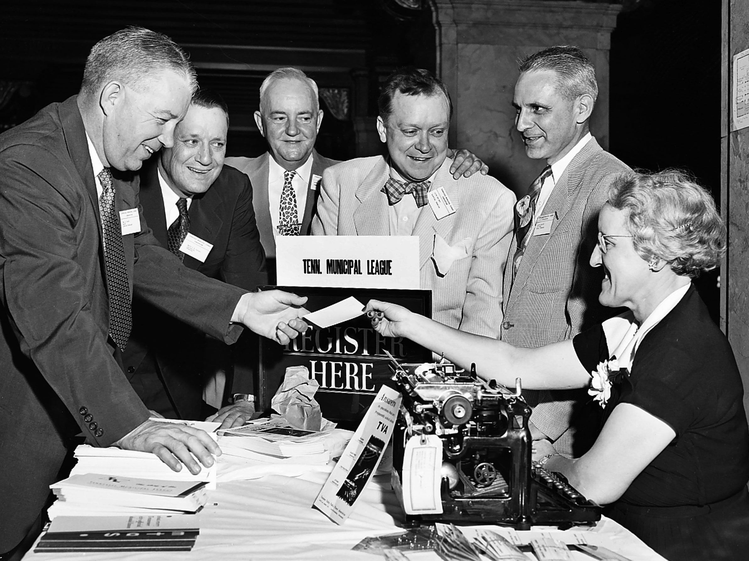 The reception desk at the Peabody was a busy place June 7, 1953 as top officials from all over the state registered for the annual Tennessee Municipal League meeting. Mayor Frank Tobey, third left, of Memphis was host. Others are, from left, Mayor W.D. Baird of Lebanon, TML president; Mayor P.R. Olgiati of Chattanooga; Mayor Ben West of Nashville; Armond Arnurius of Norris, city recorder; and Mrs. Joe Dixon of Nashville, TML secretary.