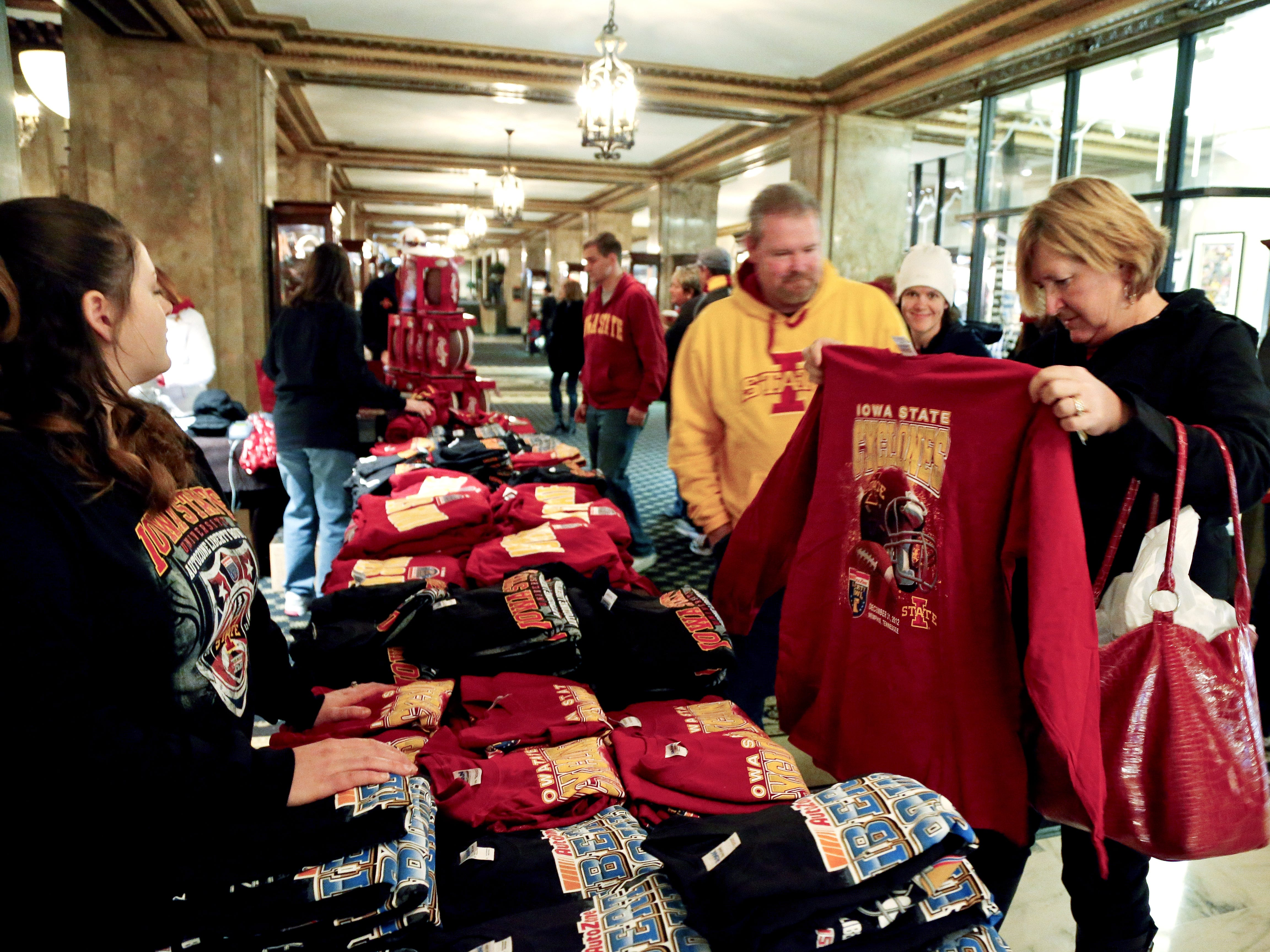 Iowa State Cyclones fans Bill and Jan Mishler of Tiffin, Iowa, check out Liberty Bowl T-shirts in the lobby of the Peabody Hotel in Memphis on Dec. 29, 2012.
