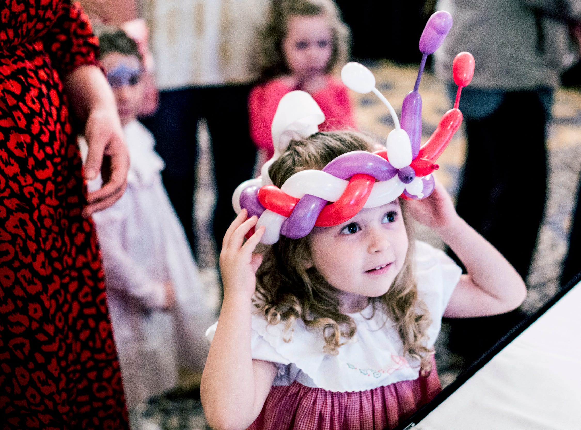 Rose Walker, 4, tries on her balloon crown during the Memphis Jingle Bell Ball Holiday Cookie Party inside of the Continental Ballroom at the Peabody Hotel on Dec. 2, 2018. This was the 30th anniversary of the Jingle Bell Ball.