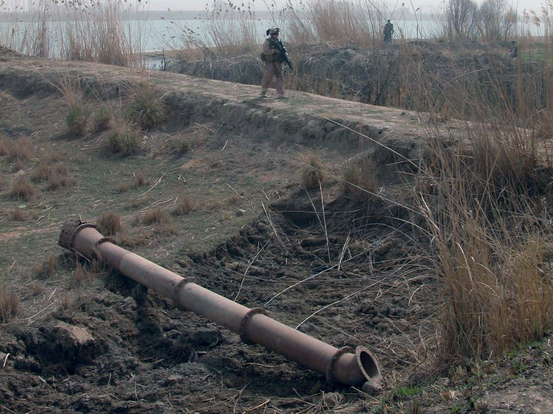 Cpl. Gregory Patterson of Waupun walks along farm fields next to the Euphrates River with Iraqi police searching for weapons and bombs buried in the ground by insurgents. A piece of irrigation pipe is in the foreground.