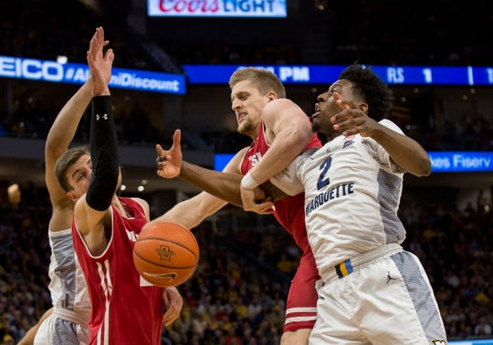 Wisconsin guard Brevin Pritzl, center, grabs a rebound from Marquette forward Sacar Anim, right, during the first half of an NCAA basketball game Saturday, Dec. 8, 2018, in Milwaukee. (AP Photo/Darren Hauck) ORG XMIT: WIDH102
