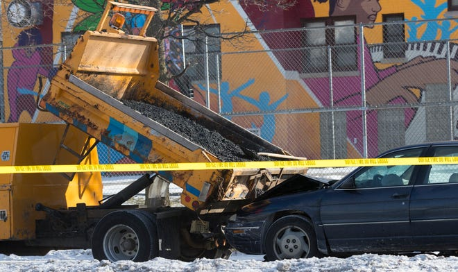 A Milwaukee police crash reconstruction team works at the scene of a collision between a City of Milwaukee Department of Public Works truck and a sedan Friday morning in the 1700 block of West Vine Street.