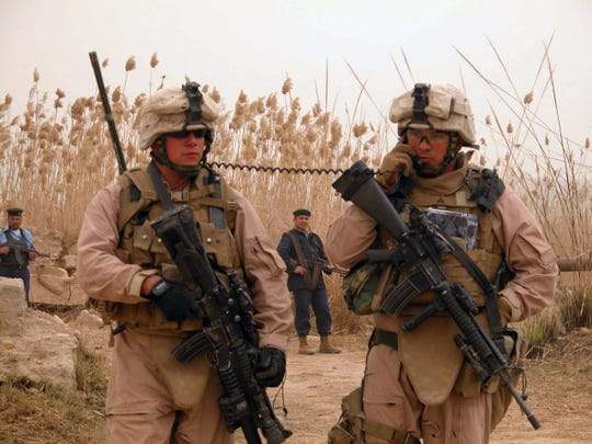 Cpl. Jose Gonzalez, 24, of Kenosha  (right), talks on a radio carried by Lance Cpl. Terry Medema, 24, of Waupun. Gonzalez was calling his commander to tell him that Iraqi police officers had discovered two 67-millimeter rockets on a bank of the Euphrates River near Hamimiyah in Anbar Province.