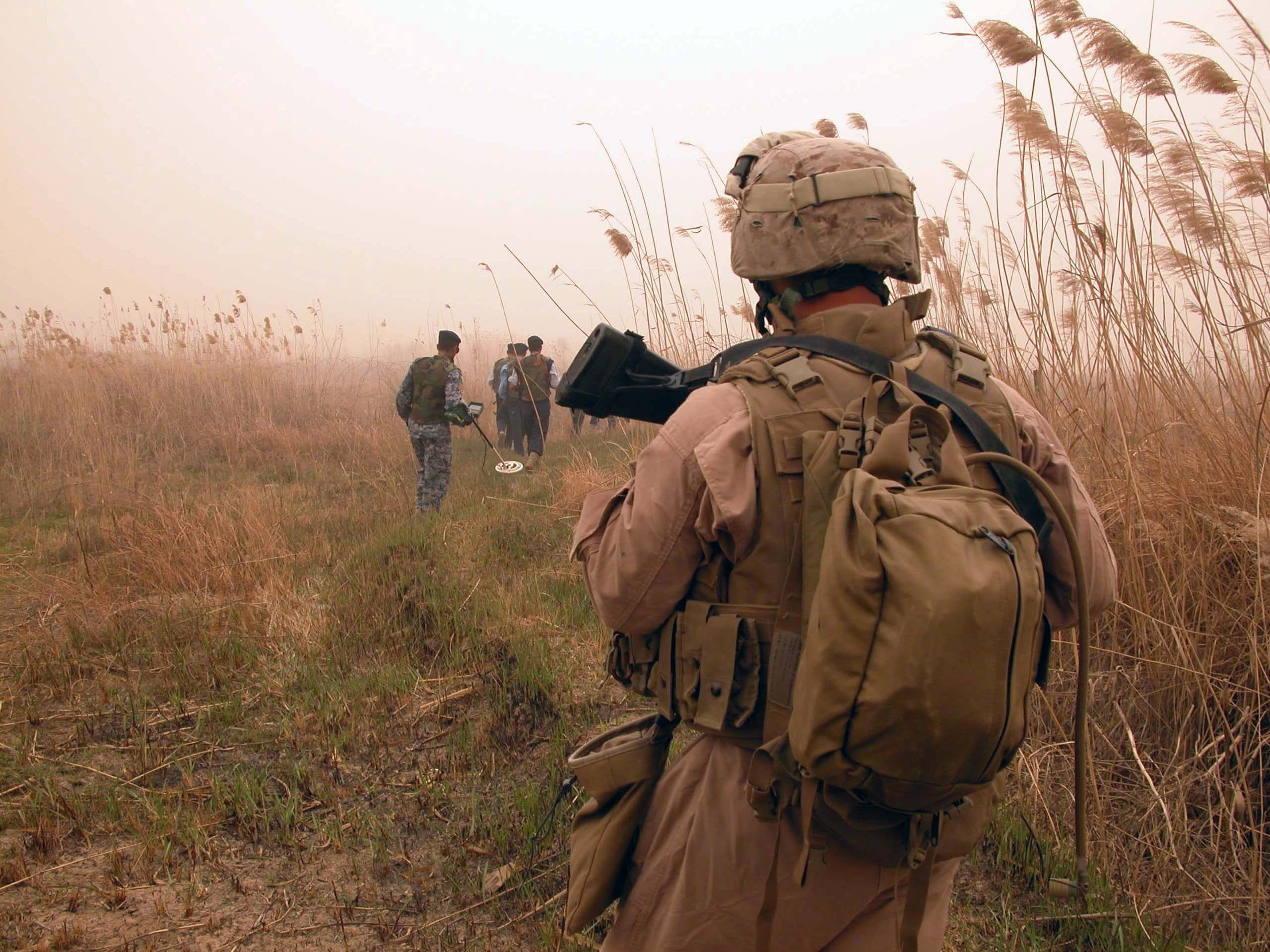 Cpl. Jose Gonzalez, a carpenter from Kenosha, walks behind Iraqi police officers searching for bombs and weapons during a foot patrol near the Euphrates River in Anbar Province. Gonzalez is a member of Fox Co., 2nd Battalion, 24th Marines.