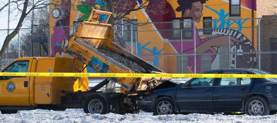 A Milwaukee police crash reconstruction team is shown at the scene of a collision between a City of Milwaukee Department of Public Works truck and a sedan.