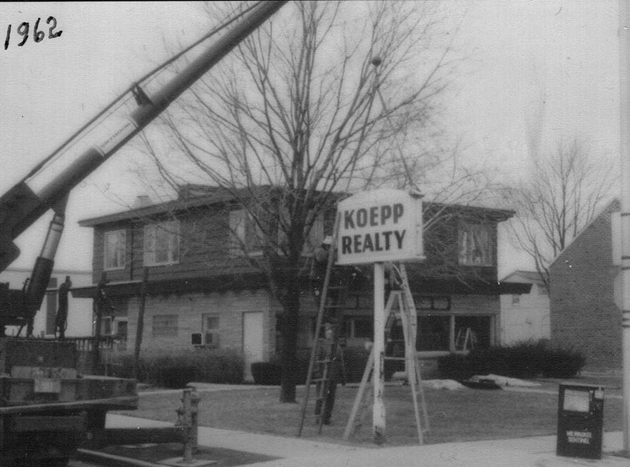 A sign being erected aKoepp Realty in 1962. The realty firm was founded by Jack Koepp in 1946