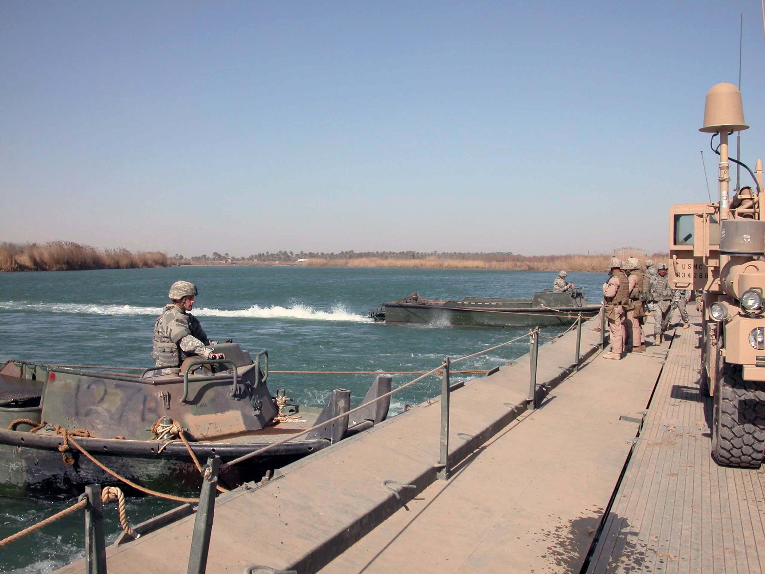 U.S. Army engineers  move a barge carrying Fox Company Marines and their vehicles across the Euphrates River in Anbar Province.