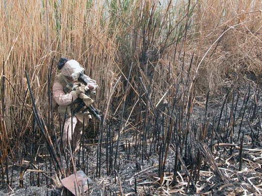 Cpl. Gregory Patterson of Waukesha snaps a photo of the rusty, twisted remains of a rocket-propelled grenade launcher found in weeds near the Euphrates River during a foot patrol searching for weapons and bombs.