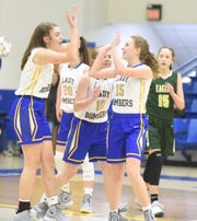 Mountain Home Junior Lady Bombers Annie Norcross, Abigail Hodges and Haven Klinger congratulate each other during a game earlier this season.
