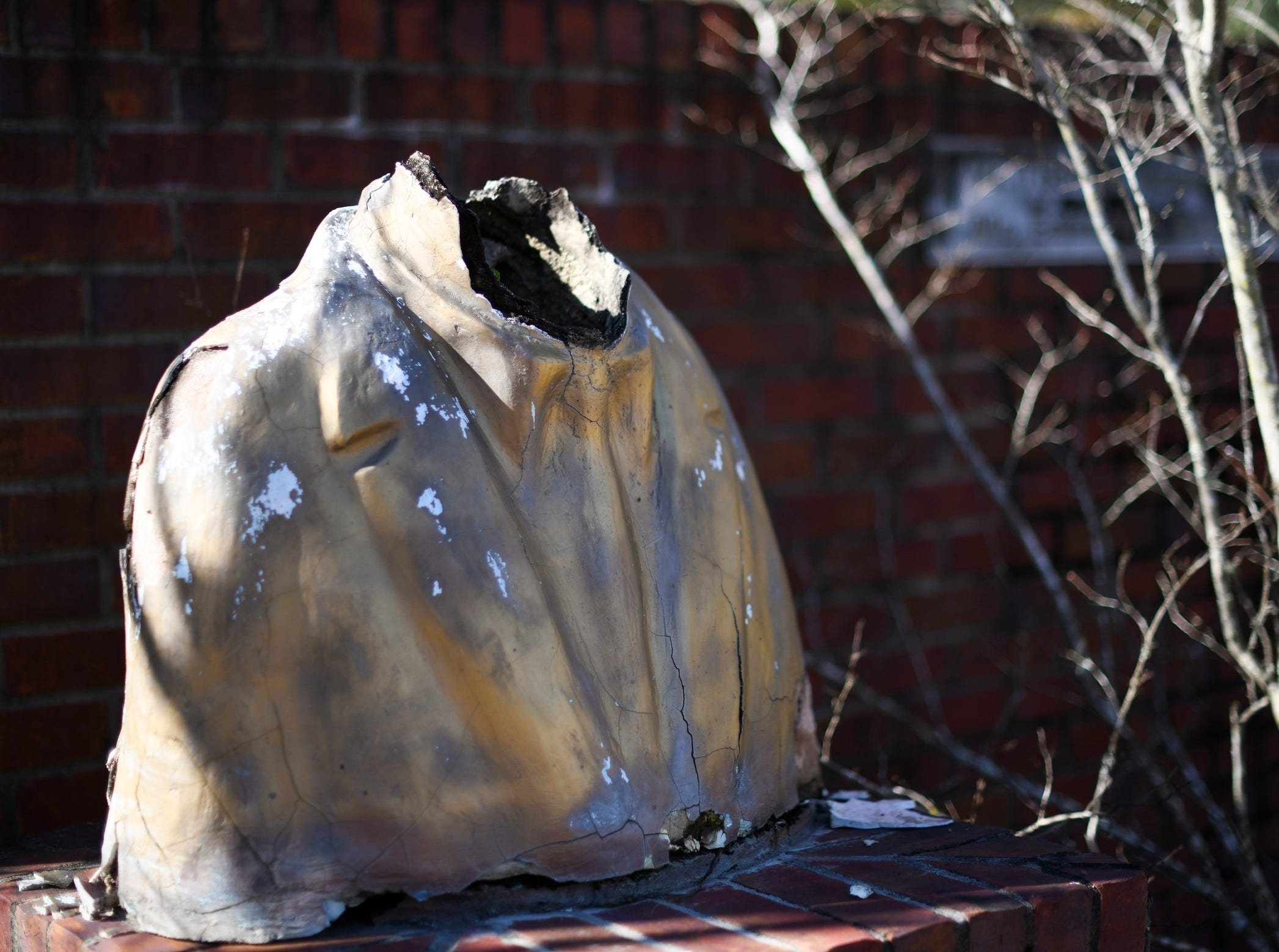 A vandalized bust remains on display at what was the Africatown Welcome Center in Mobile, Ala., on Tuesday, Jan. 29, 2019. The center was destroyed by Hurricane Katrina in 2005, and hasn't been rebuilt. (AP Photo/Julie Bennett)