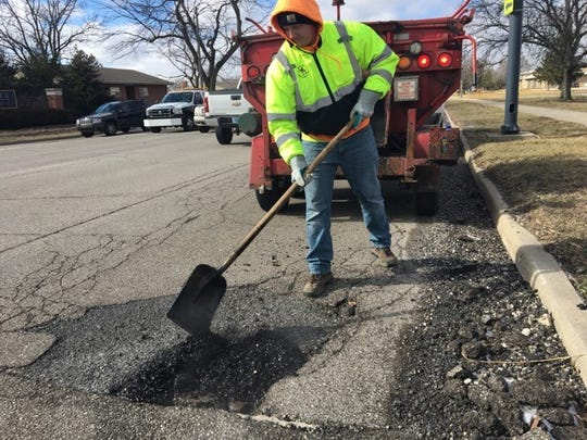 Aaron Holding, a CDL driver with the city street department, works to patch a pothole near the intersection of Bethel and McKinley avenues Friday, Feb. 8, 2019.