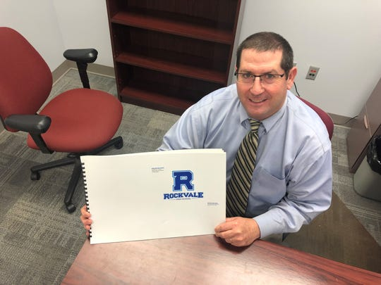 Rockvale High principal Steve Luker holds up one sample of the school's logo.