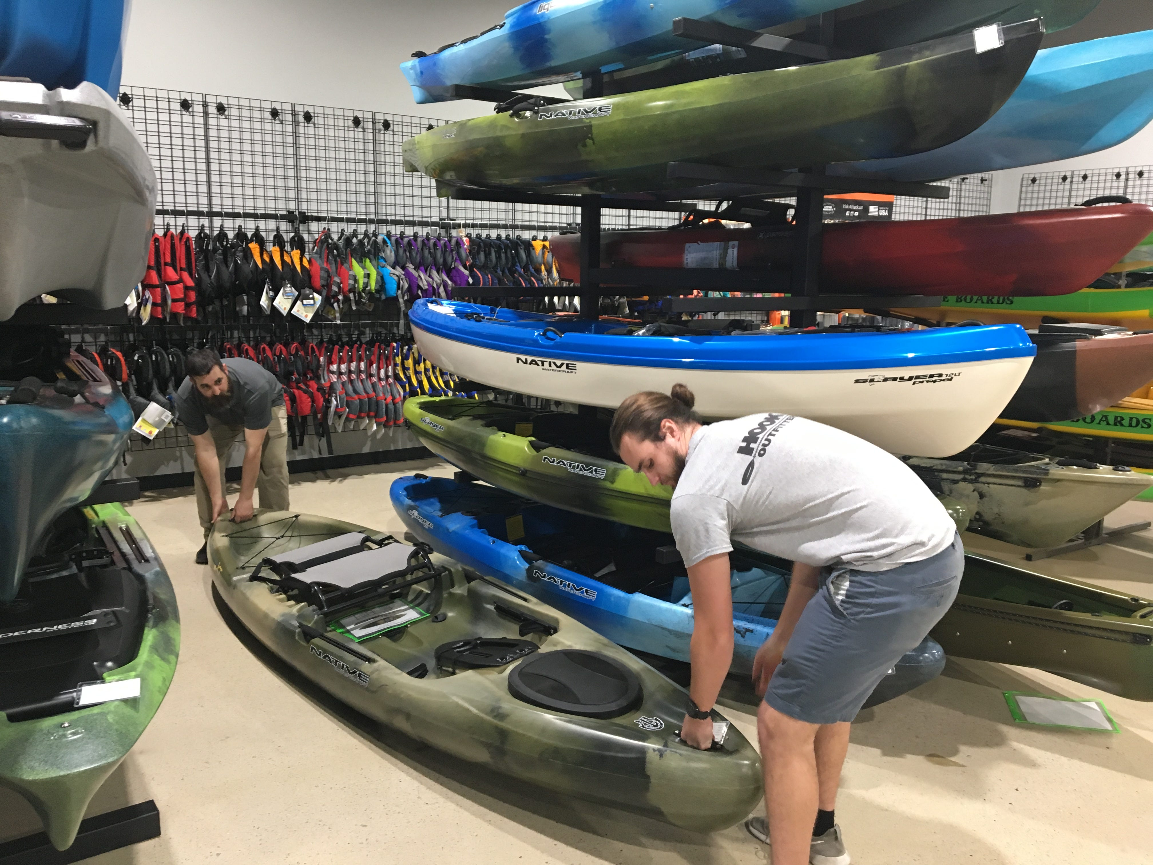 Chris Conder, manager of Murfreesboro's Hook 1 outfitters, and Tanner Morris, a whitewater enthusiast, lift one of the kayaks at the newly opened store.