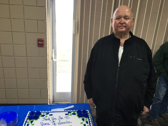 Officer Benny Adams stands next to a cake celebrating his 45 years with the Gallatin Police Department.