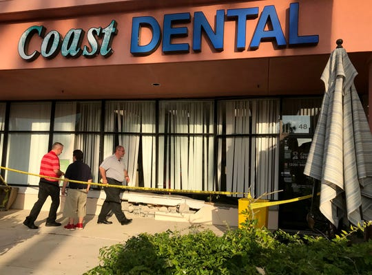 Workers from Fireservice Disaster Kleenup remove debris from Coast Dental in Bonita Bay Plaza after a car crashed into the dental office, injuring two people inside.