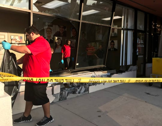Workers from Fireservice Disaster Kleenup remove debris from Coast Dental in Bonita Bay Plaza after a car crashed into the dental office Friday afternoon, injuring two people inside the office.