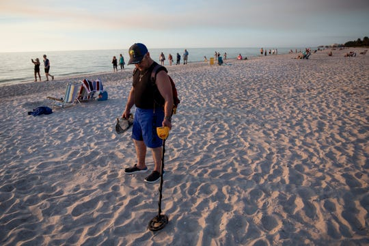 Salvatore Collana searches for coins and jewelry using his metal detector at the Naples Pier in Naples, on Thursday, February 7, 2019. Collana, who lives near Buffalo, New York, for most of the year and spends his winters in Naples with his father, says that looking for lost treasures on the beach is part of his usual routine.