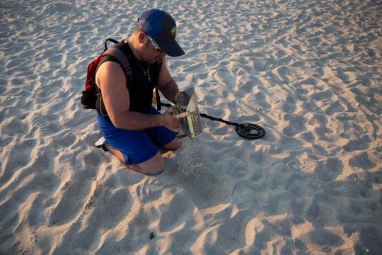 Salvatore Collana digs in the sand after picking up a signal with his metal detector at the Naples Pier in Naples, on Thursday, February 7, 2019. Collana didn't find any jewelry on Thursday, mostly just dimes and tin foil.