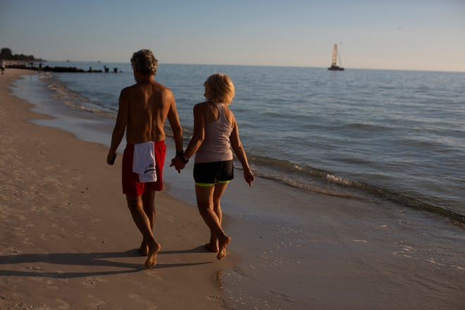 Gheza and Jen Sczabo walk on the beach together at Lowdermilk Park in Naples on Feb. 7, 2019. The couple, on vacation from Toronto, Canada, has been married for 37 years.