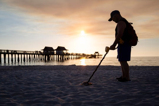 Salvatore Collana searches for coins and jewelry using his metal detector at the Naples Pier in Naples, on Thursday, February 7, 2019. Collana often finds pop tabs and tin foil while searching the beach, but says you have to dig the trash to find the treasure.