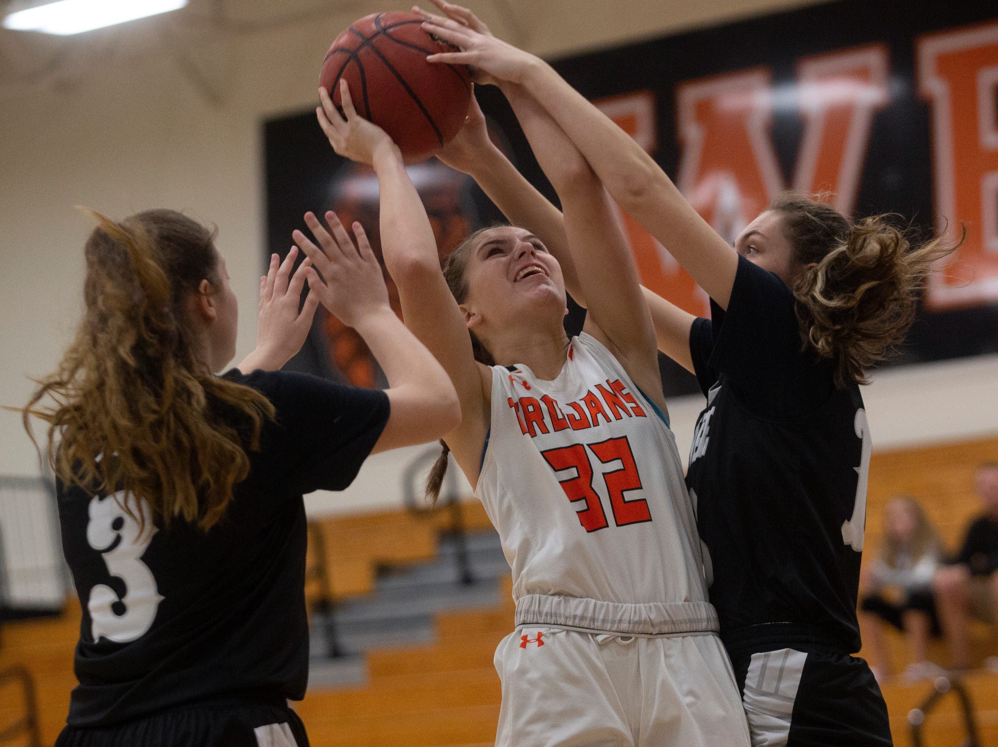 Lely High School's Katie Miller attempts a shot as Mariners' Brianna Childs and Carlee Groeneveld defend the basket, Thursday, Feb. 6, 2019, at Lely High School.