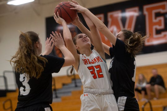 Lely High School's Katie Miller attempts a shot as Mariner's Brianna Childs and Carlee Groeneveld defend the basket in the Class 6A-District 12 championship game on Thursday at Lely.