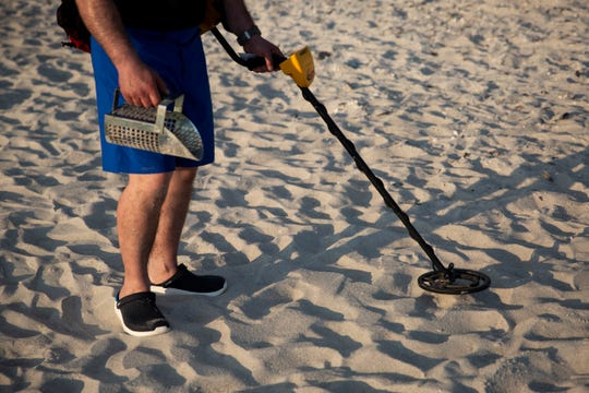 Salvatore Collana searches for coins and jewelry using his metal detector at the Naples Pier in Naples, on Thursday, February 7, 2019.