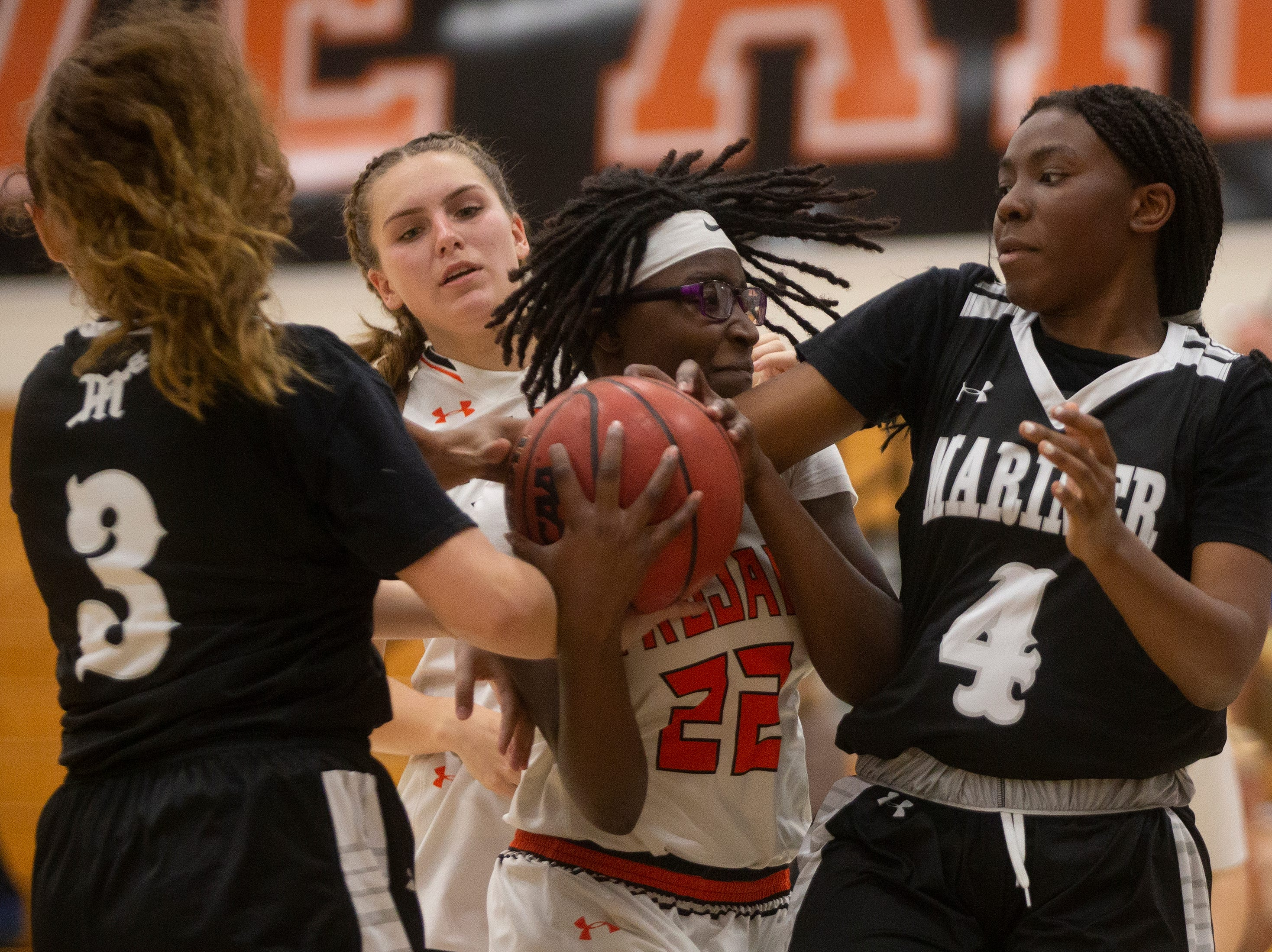 Lely High School's Kenya Stuart fights for the rebound against Mariners High School's Brianna Childs, left, and Naomi Darrett, Thursday, Feb. 6, 2019, at Lely High School.