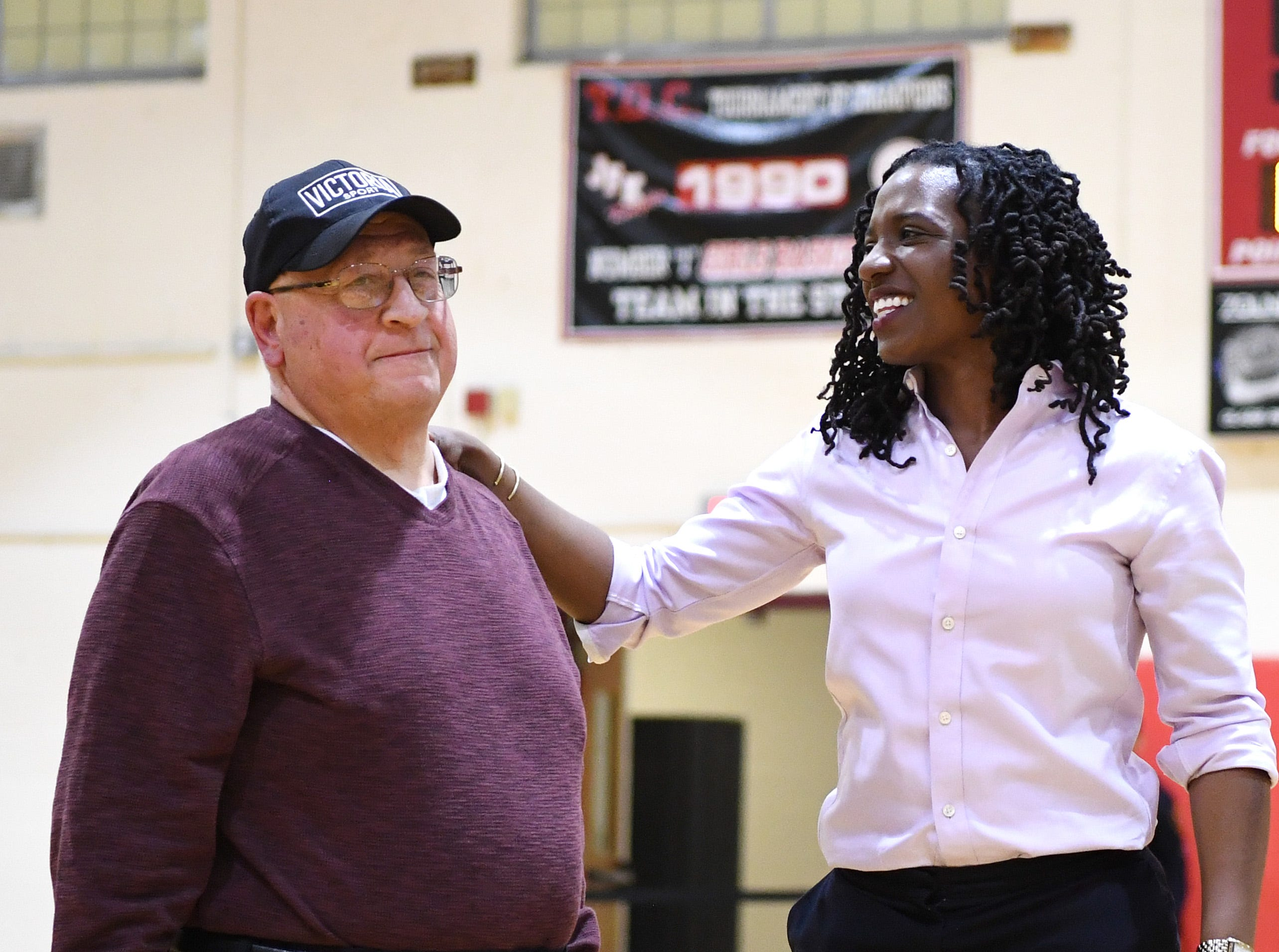 (center) Nicole Louden, who graduated from Kennedy High School in 2001 with a career total of 2,928 points, is honored in a pregame ceremony before the start of a Kennedy girls varsity basketball home game on Thursday, February 7, 2019. (left) Lou Bonora, who coached Louden her senior year.