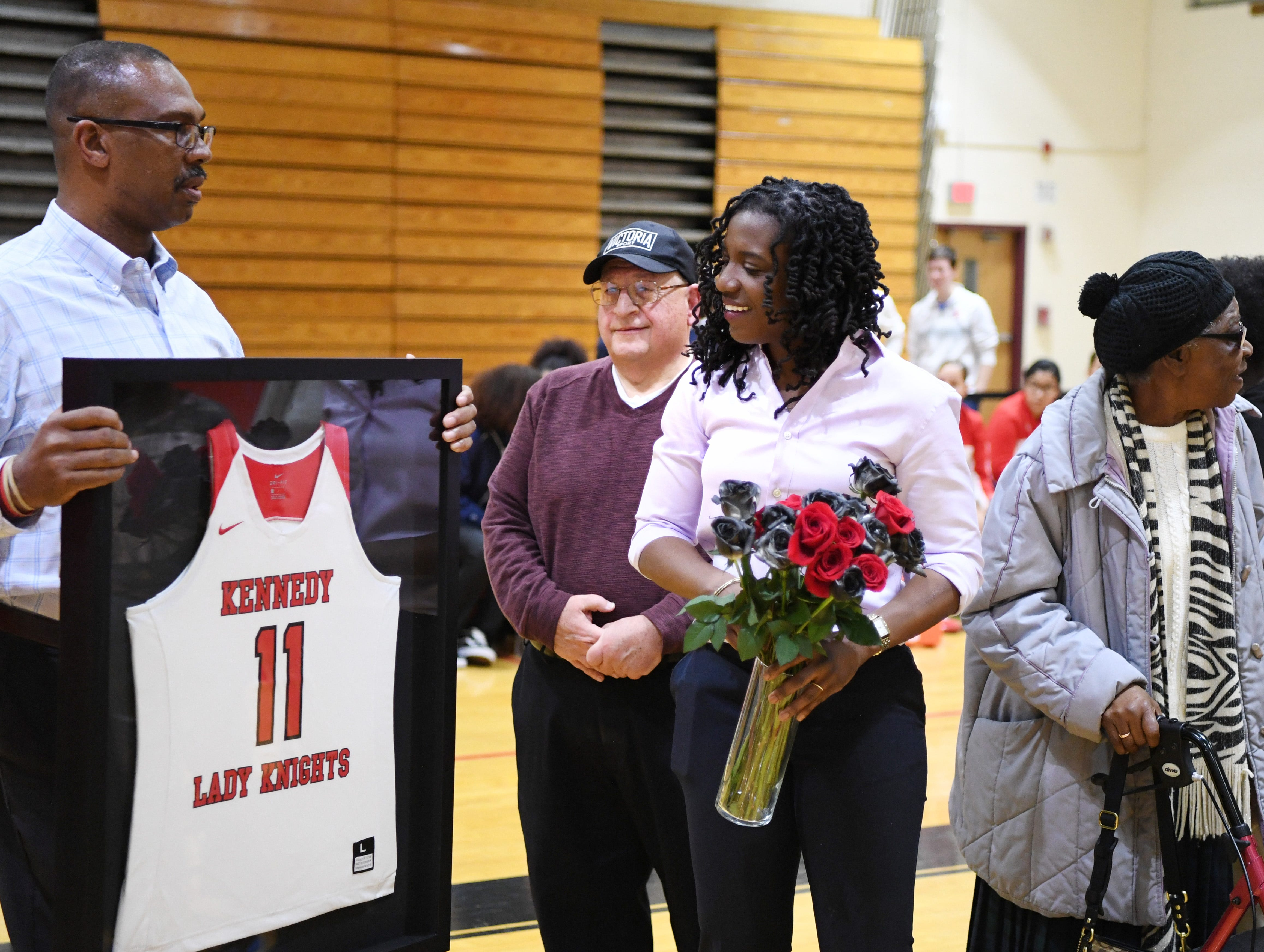 (center) Nicole Louden, who graduated from Kennedy High School in 2001 with a career total of 2,928 points, is honored in a pregame ceremony before the start of a Kennedy girls varsity basketball home game on Thursday, February 7, 2019. (from left) Athletic Director Scott Durham and Lou Bonora, who coached Louden her senior year.