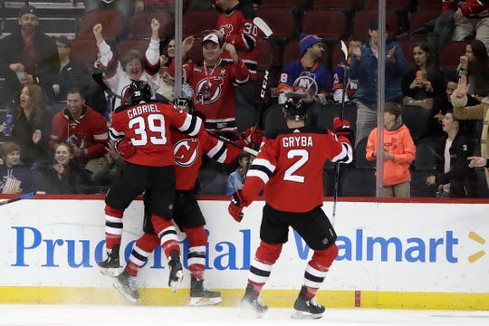 New Jersey Devils right wing Kurtis Gabriel (39) jumps onto forward Kevin Rooney, center, as defenseman Eric Gryba (2) looks on after Rooney scored a goal against the New York Islanders during the first period of an NHL hockey game Thursday, Feb. 7, 2019, in Newark, N.J.