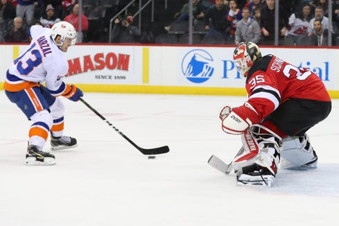 Feb 7, 2019; Newark, NJ, USA; New York Islanders center Mathew Barzal (13) scores a goal past New Jersey Devils goaltender Cory Schneider (35) during the first period at Prudential Center.