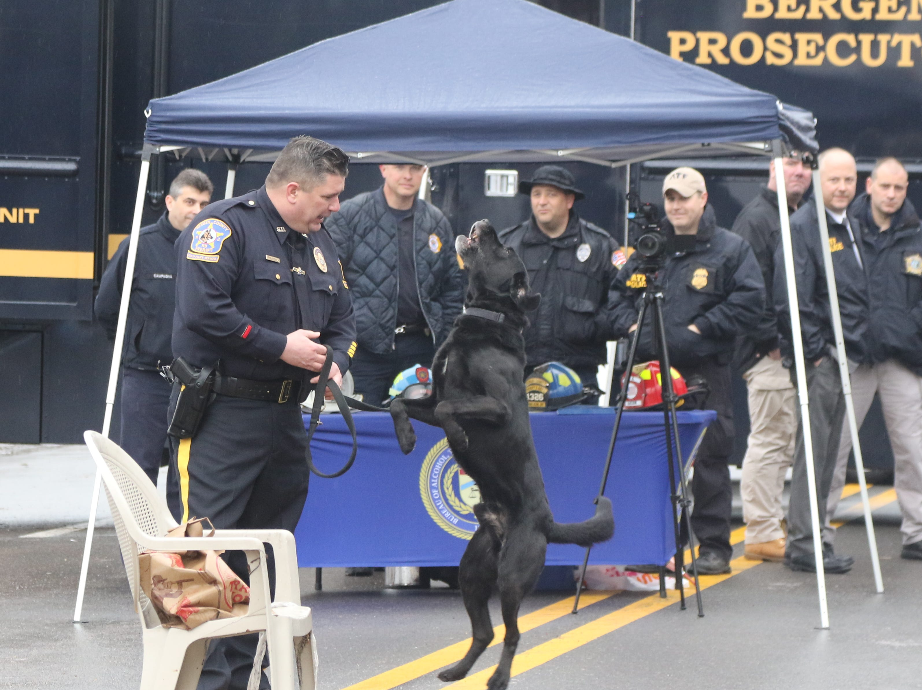 Bergen County Sheriff's Officer Les Lorenc with his dog Bubba before he shows how his dog sniffs out possible accelerants as part of a demonstration on the street outside the gates of the devastated paper company. The Bureau of Alcohol, Tobacco and Firearms along with the NJ State Fire Marshall and the Bergen County Sheriff's Office demonstrate how specially trained dogs sniff out possible accelerants and explosives that may have possibly been used at the site of the Marcal fire. The demonstration took place at the Marcal site on February 8, 2019.