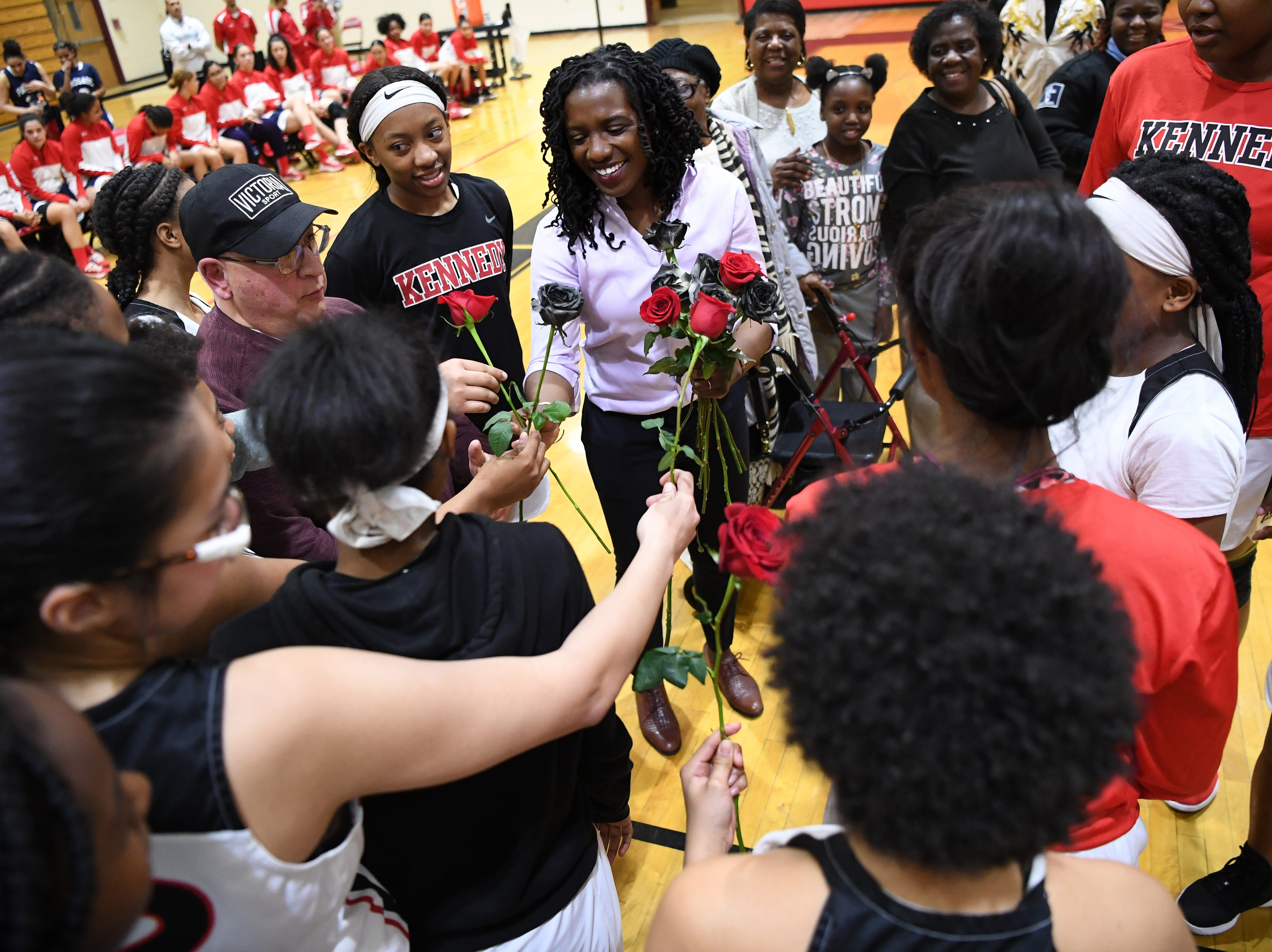 (center) Nicole Louden, who graduated from Kennedy High School in 2001 with a career total of 2,928 points, is honored in a pregame ceremony before the start of a Kennedy girls varsity basketball home game on Thursday, February 7, 2019. Louden is given roses by members of the Kennedy girls varsity basketball team.