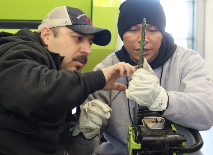 San Juan County Fire Department Division Chief David Vega shows Youth Conservation Corps member Sanchez Curley how to check the blade on a chainsaw on Thursday at the Bloomfield Fire Department station.