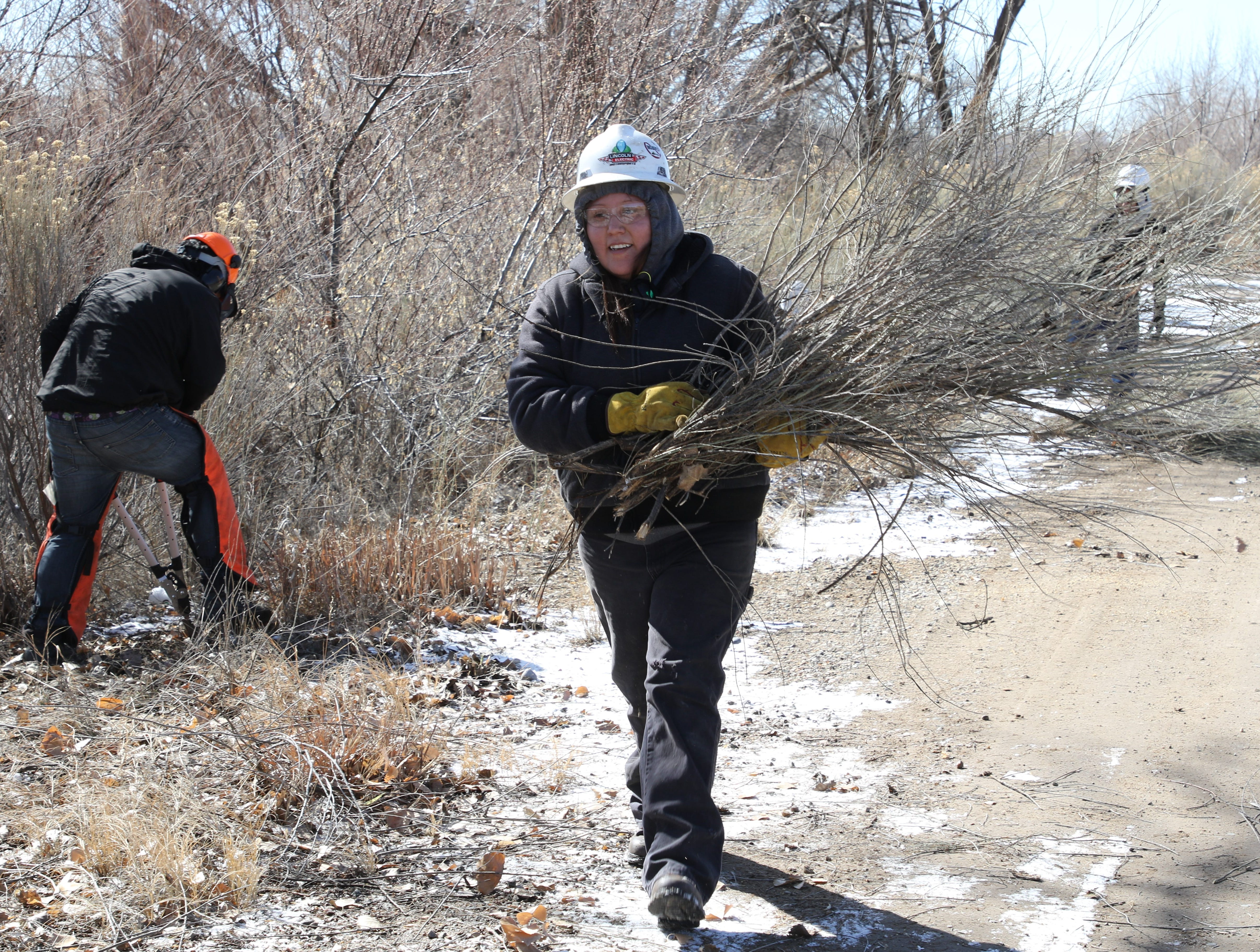 Youth Conservation Corps member Brandie Lee, center, carries debris from the group's work site north of the city of Bloomfield ponds on Thursday.