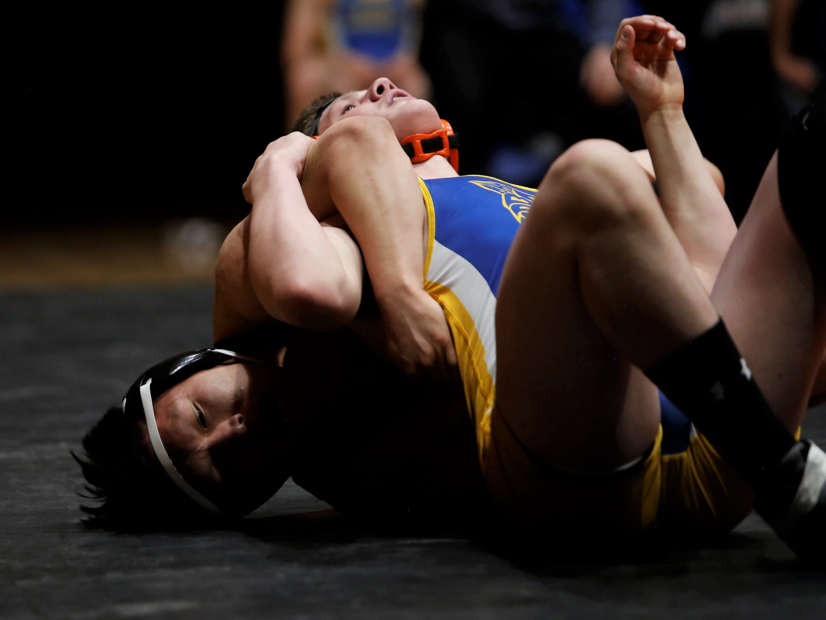 Aztec's Malcolm Altisi pulls back Bloomfield's Gerald Wiza by the right arm in the 170-pound division match during Thursday's District 1-4A duals at Lillywhite Gym in Aztec. Wiza won via 5-1 decision.