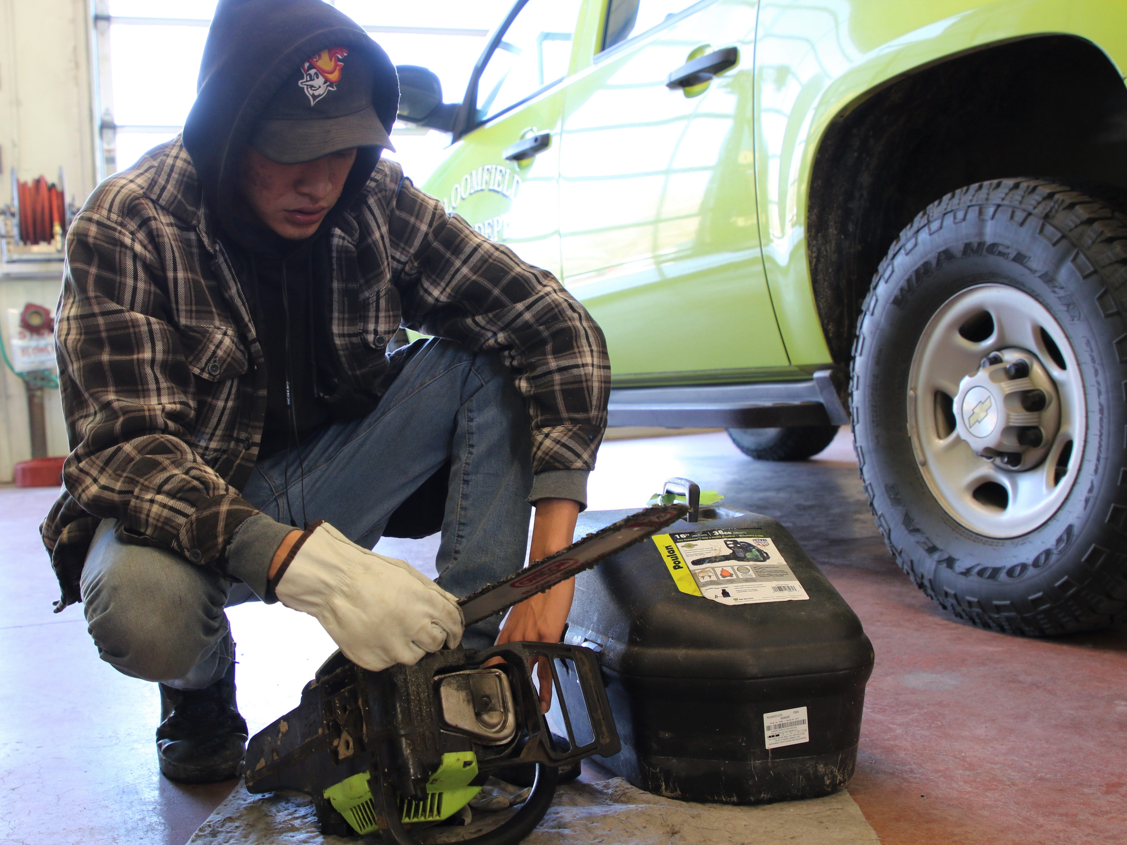 Youth Conservation Corps member Xavier David examines a chainsaw during a maintenance inspection on Thursday at the Bloomfield Fire Department station.