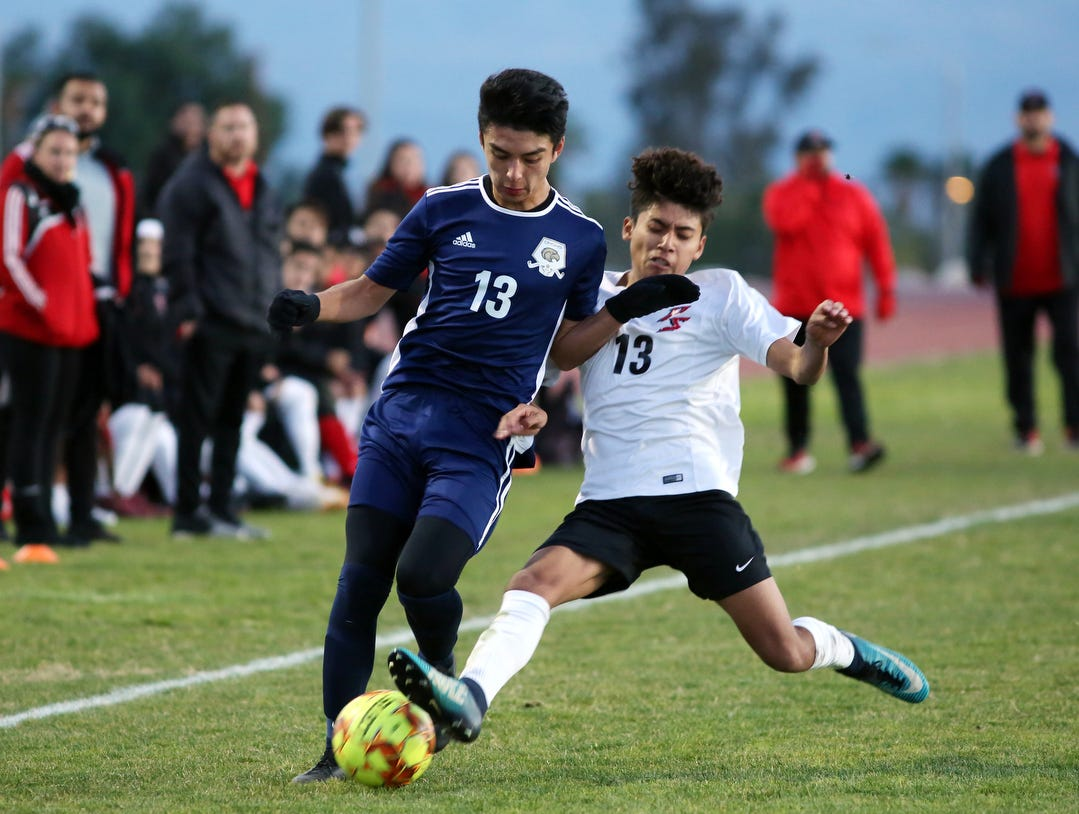 Desert Hot Springs' Miguel Hernandez, left, and Palm Springs' Romauldo Cuamani battle for the ball during the CIF round one playoff game against Palm Springs in Desert Hot Springs on Thursday, February 7, 2019. Desert Hot Springs won 3-2.