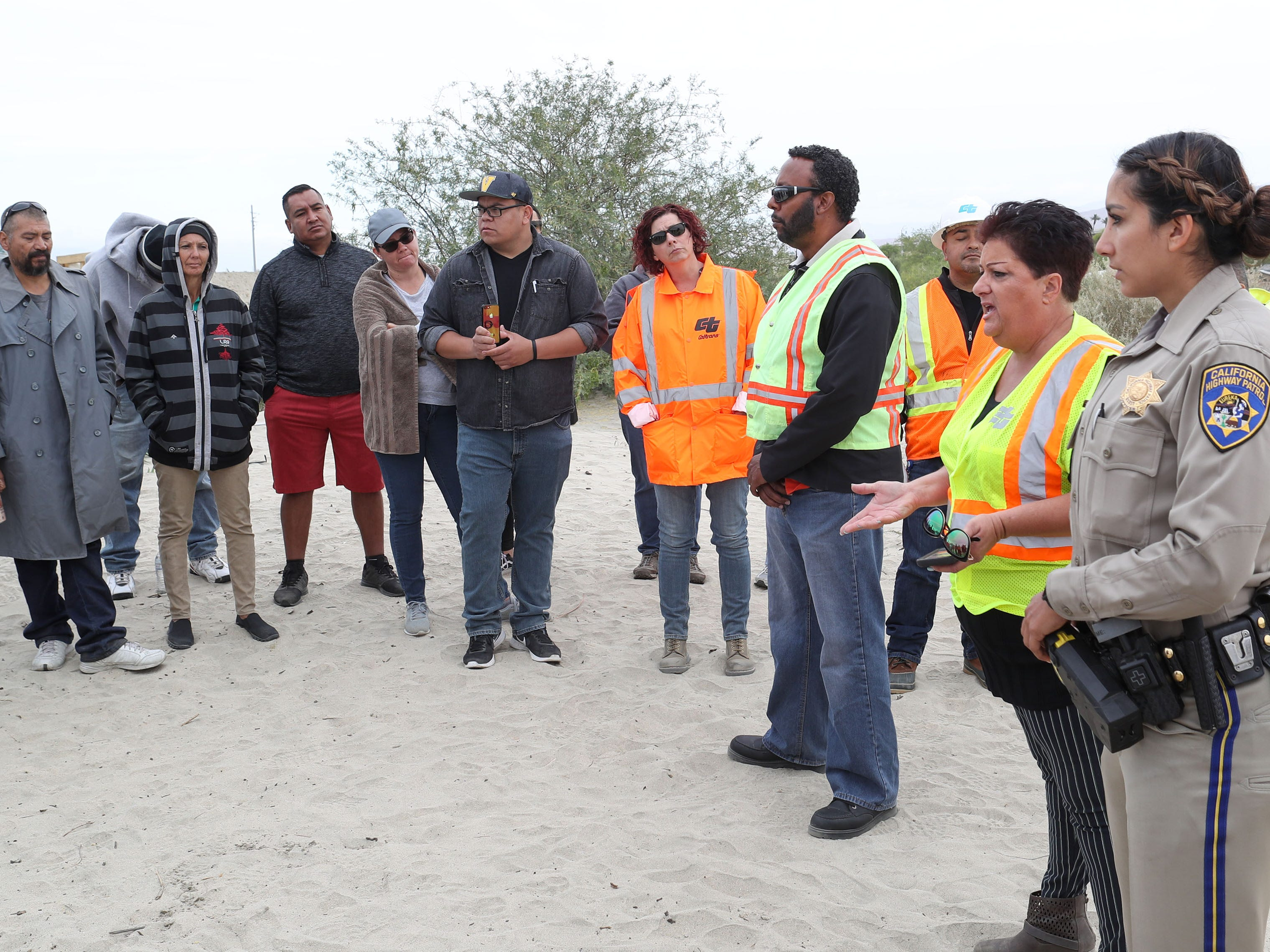 Caltrans spokeswoman Terri Casinga, second from right, informs those living at the Coachella encampment that they will have to leave the property, May 1, 2018.