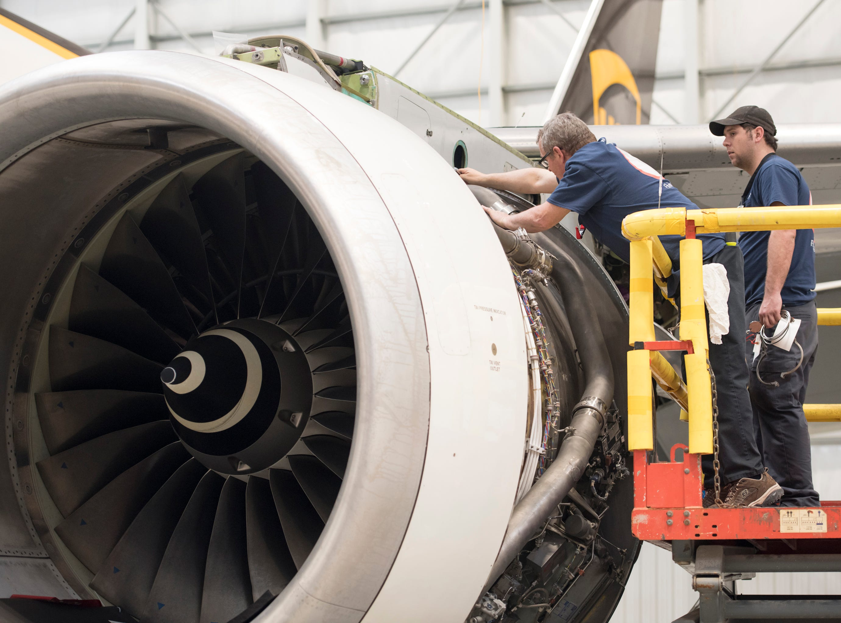 Mechanics Eric Matherly, left, and Justin Wilson work on a jet engine in the hangar at ST Engineering at the Pensacola International Airport in Pensacola on Friday, February 8, 2019.