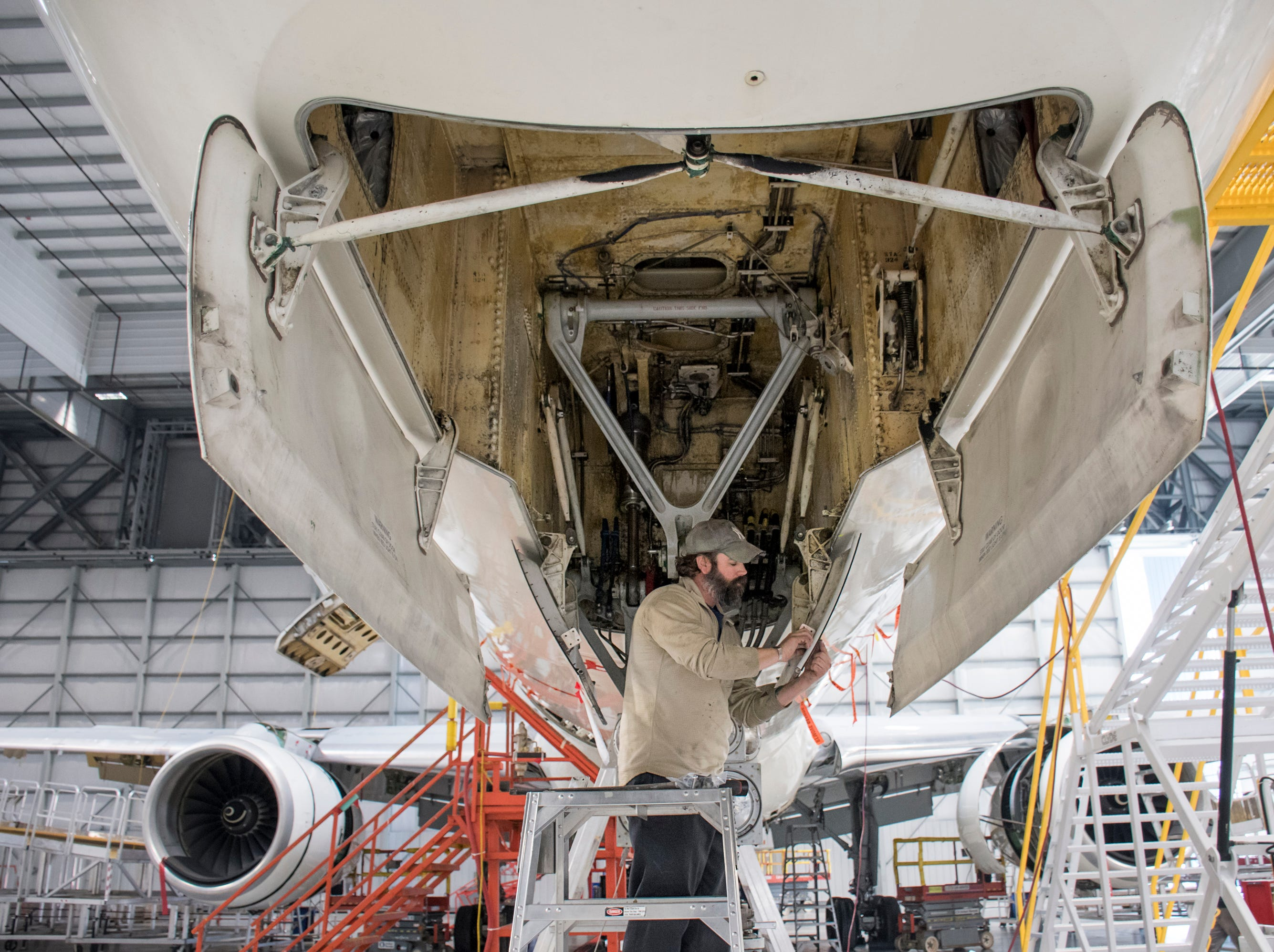 Mechanic Damion Vaughn works on an airplane at ST Engineering at the Pensacola International Airport in Pensacola on Friday, February 8, 2019.