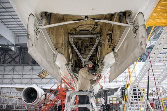 Mechanic Damion Vaughn works on an airplane Friday at the ST Engineering hangar at the Pensacola International Airport. The Triumph Gulf Coast board has approved granting an additional $10 million, on top of the previously granted $66 million, for a project to expand the company's aircraft maintenance, repair and overhaul facility at the airport.