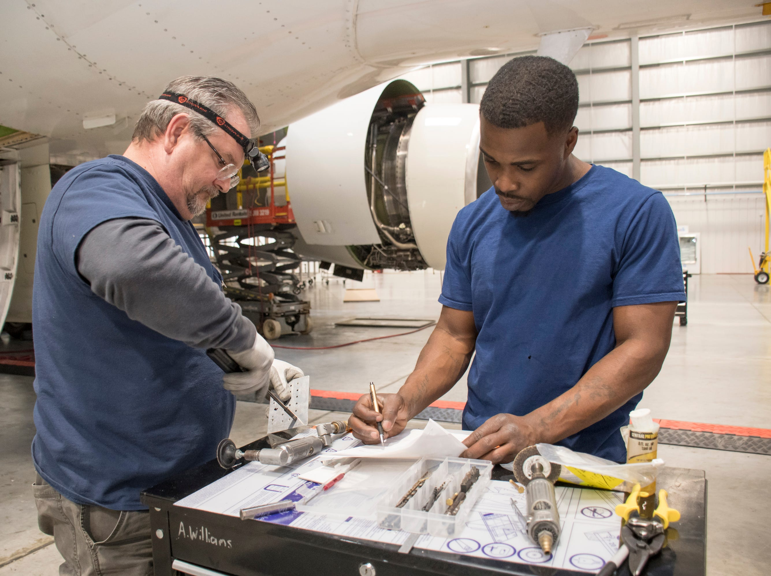 Sheet metal mechanics Greg Larson, left, and Antwonn Williams work at ST Engineering at the Pensacola International Airport in Pensacola on Friday, February 8, 2019.