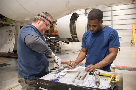Sheet metal mechanics Greg Larson, left, and Antwonn Williams work Feb. 8 on an airplane at ST Engineering's hangar at the Pensacola International Airport.